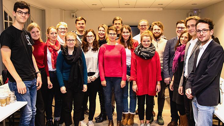 Studierendengrupe im Seminarraum lächelnd in die Kamera blickend