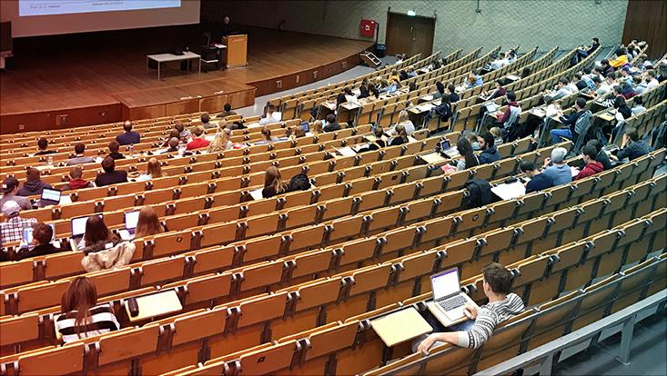 vereinzelte Studierende sitzen im Audimax bei einer Vorlesung