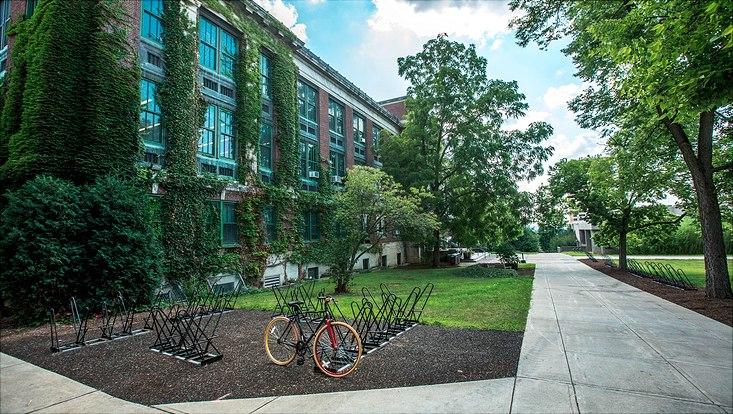 Großes Gebäude mit Fassadenbegrünung. Davor sind Fahrradständer mit einem Fahrrad