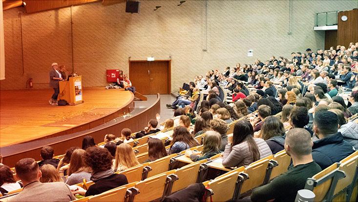 Mitarbeiterinnen halten einen Vortrag im Audimax zur Welcome Week