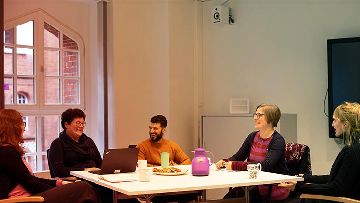 Mitarbeitende des Schreibzentrums sitzen an einem Tisch, lachelnd, gemeinsam mit einer Wissenschaftlerin aus Dänemark