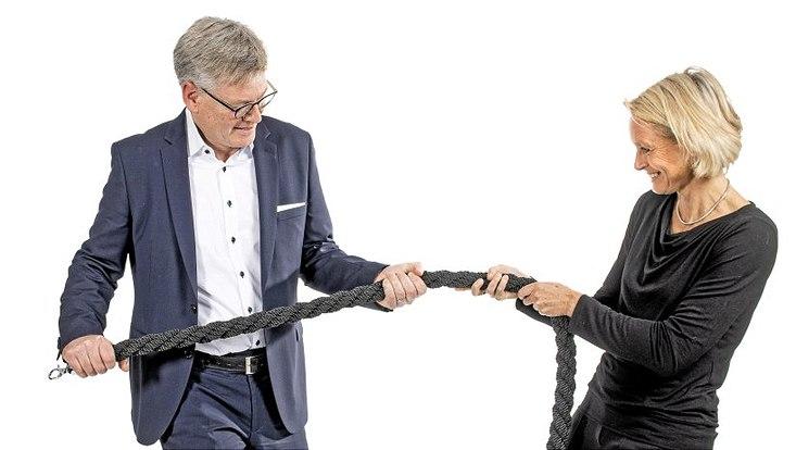 Sonja Nielbock und Dr. Jens Joachim Rogmann ziehen an einem schwarzen Seil in entgegengesetzten Richtungen.