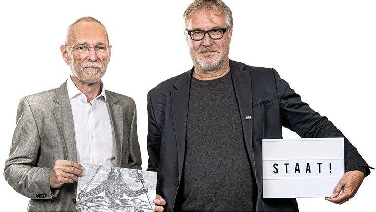 """Prof. Dr. Olaf Asbach (links) hält ein Bild in den Händen. Prof. Dr. Arne Heise hält einen Kasten auf dem """"STAAT !"""" steht."""