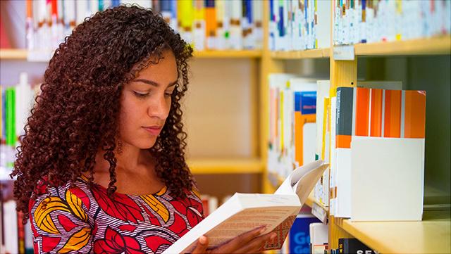 Eine Studentin steht vor dem Bücherregal und liest aus einem der Bücher.