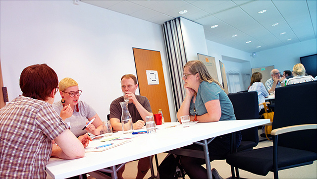 Studierende und Lehrende tauschen sich an einem Tisch miteinander aus, im Hintergrund ein weiterer Tisch