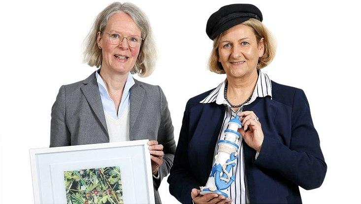 Annegret Reitz-Dinse (links) hält ein Bild in einen Rahmen in der Hand und die Prof. Dr. Beate M.W. Ratter neben ihr das Modell eines Leichturms.