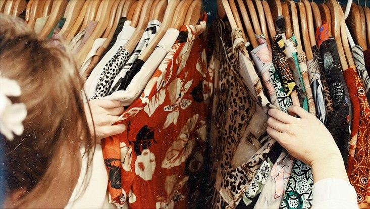 Junge Frau sieht sich Kleidung in einem Schrank an