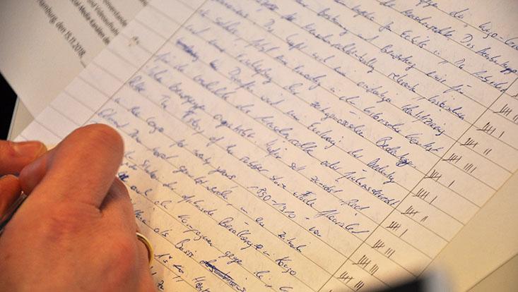 Das Bild zeigt ein beschriebenes Blatt und eine Hand, die einen Stift hält
