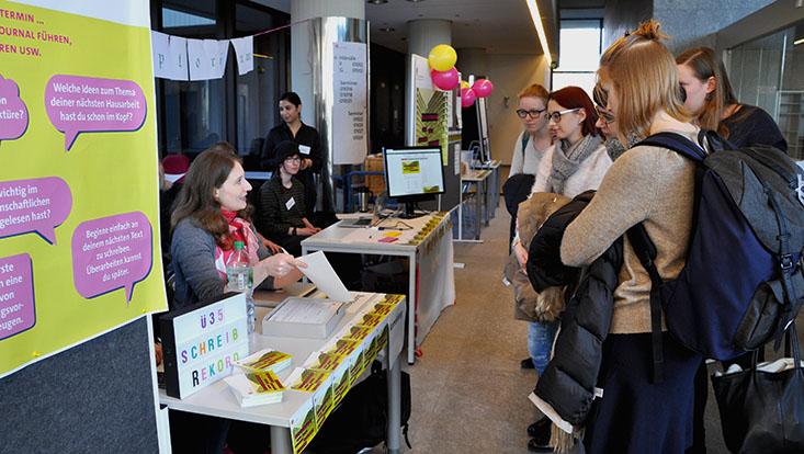 Das Bild zeigt interessierte Studierende, die sich über den Schreibrekord informieren