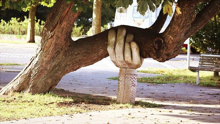 Hand aus Holz hält Baum