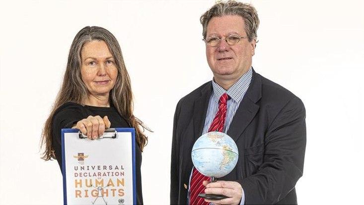 Prof. Dr. Christine Straehle hält ein Klemmbrett mit der Erklärung zu den Menschenrechten und Prof. Dr. Stefan Oeter hält einen kleinen Globus.