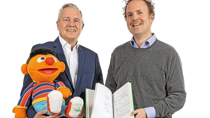 Dr. med. Johannes Hauke Staats (li.) hält eine Puppe von Ernie und Prof. Dr. Martin Jörg Schäfer ein Buch.