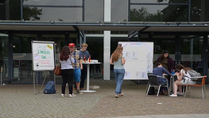 Das Bild zeigt den Info-Stand des Uk beim Diversity-Tags und interessierte Studenten