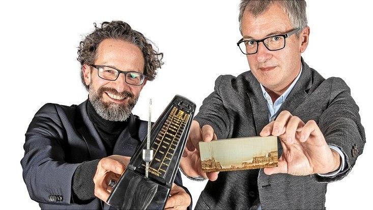 """Friedrich Geiger (l.) hält ein Metronom. Frank Fehrenbach zeigt ein von der Natur poliertes Kunstwerk aus Kalkstein (""""Ruinenmarmor"""")."""