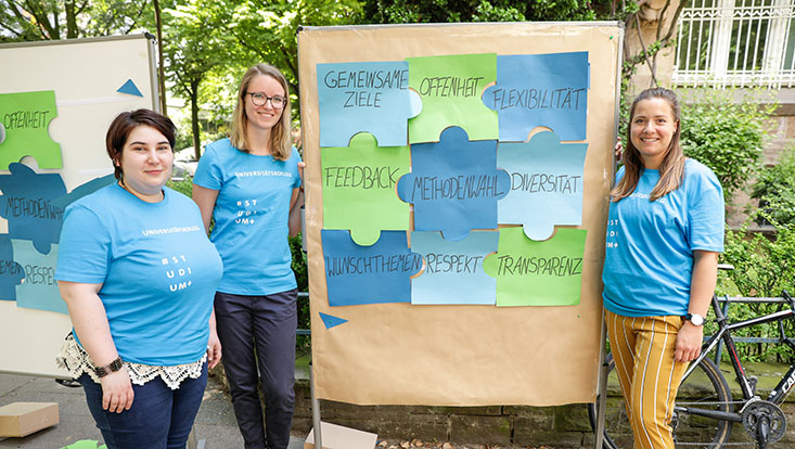 Das Bild zeigt drei Mitarbeiterinnen des Unikollegs bei ihrer selbsterstellten Puzzle-Aufgabe
