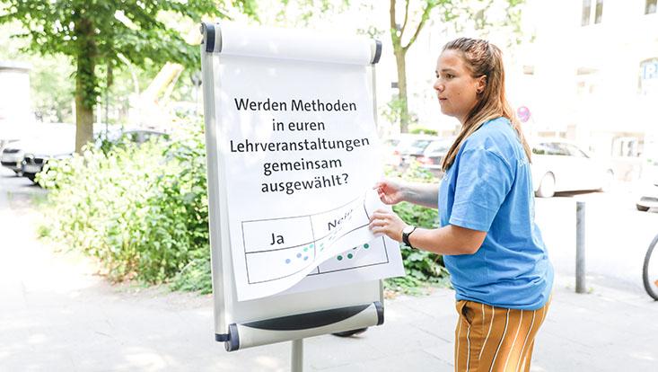 Das Bild zeigt eine Mitarbeiterin des Unikollegs mit einer Meinungsumfrage