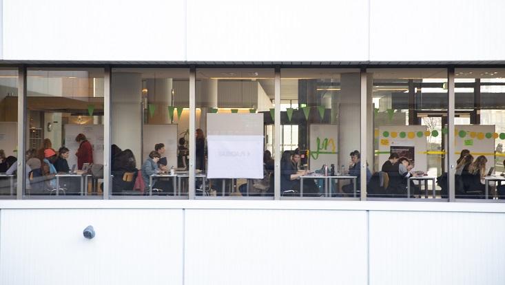 Das Bild zeigt eine Fensterfront des Überseeringgebäudes und die dahinter sitzenden Teilnehmenden des Schreibrekords