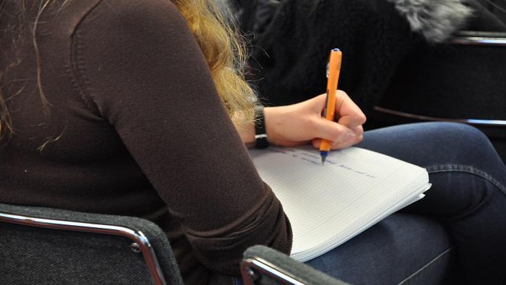 Das Bild zeigt eine Person beim Schreiben