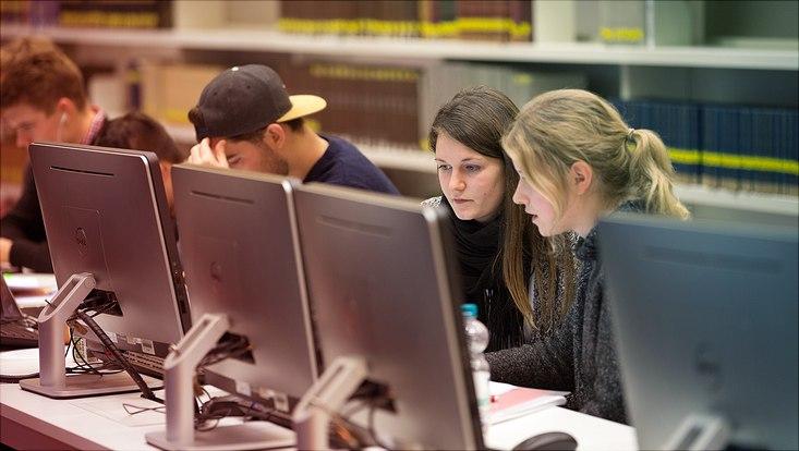 Studierende sitzen vor Monitoren.