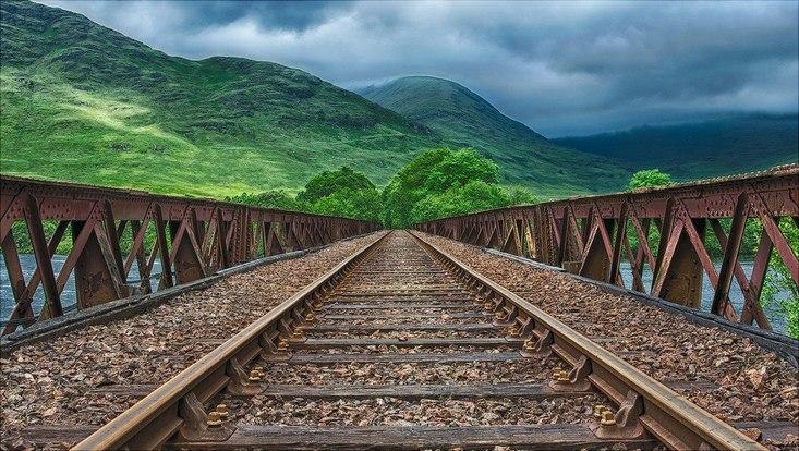 Bahnschienen führen in grüne Hügel
