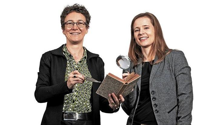 Miriam Rürup (l.) hält ein Buch mit jüdischen Märchen und einen Thora-Zeiger in der Hand. Juliane Degner hält eine Lupe.
