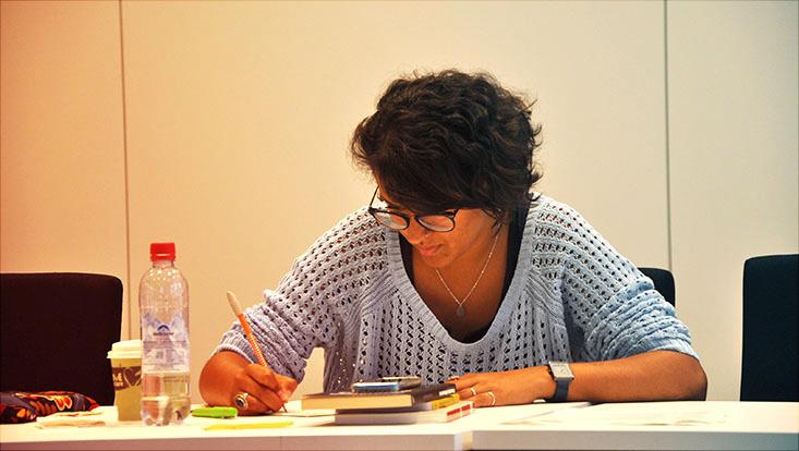 Das Bild zeigt eine schreibende Studentin.