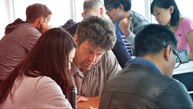 Das Bild zeigt Menschen unterschiedlichen Alters und unterschiedlicher Herkunft bei gemeinsamer konzentrierter Arbeit an Tischen..