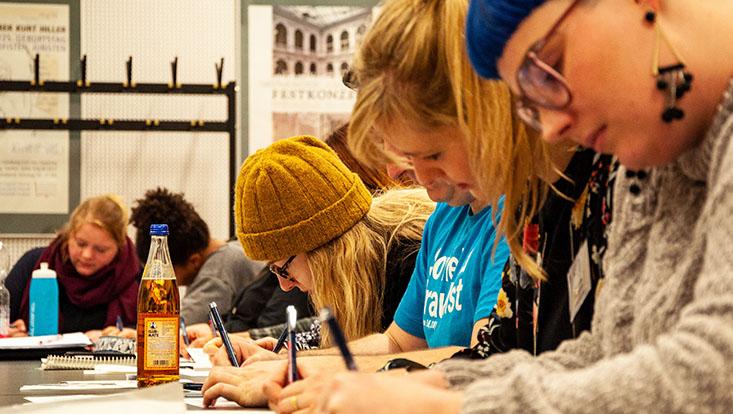 Studierende beim Schreiben in einem Seminarraum