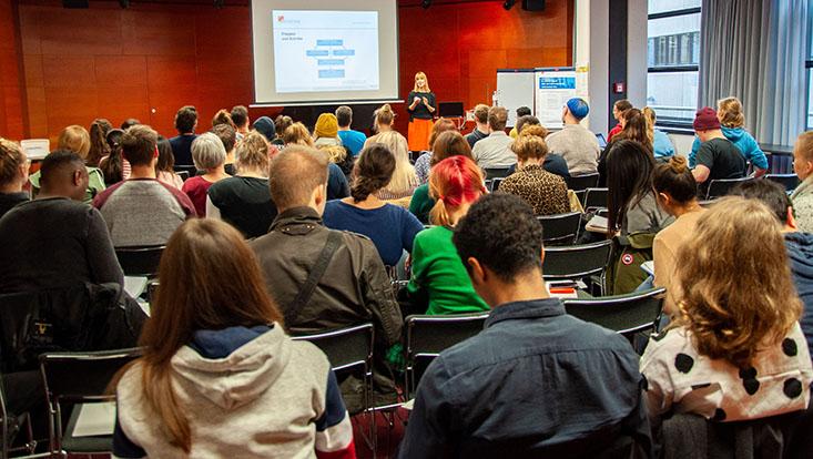 Vortragende in einem großen Raum steht vor einer Präsentation, im Vordergrund sitzen sehr viele Studierende
