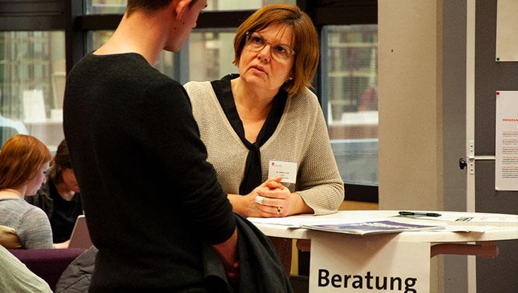 Studierender lässt sich von einer Kursleiterin beraten, an einem Tisch stehend, Schild Beratung rechts unten