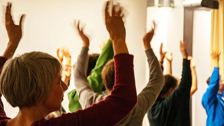eine Person ist von hinten zu sehen, sie streckt die Arme in die Höhe, weitere Arme im Hintergrund vollführen die gleiche Bewegung