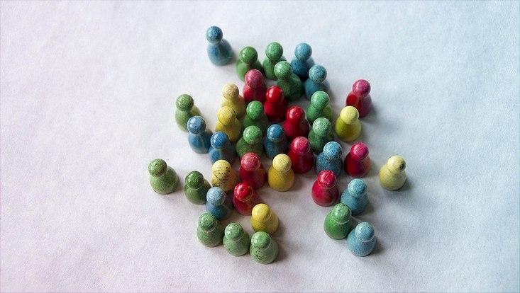 Verschiedenfarbige Spielfiguren stehen beieinander