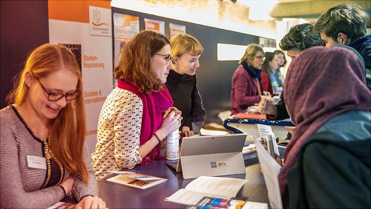 Das Bild zeigt Mitarbeiterinnen des OSA-Zentrums mit ihrem Informationsstand beim Uni-Tag 2020.