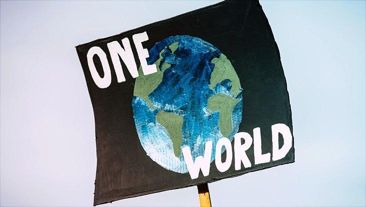 """Auf einem Schild ist der Schriftzug """"One World"""" sowie ein gemalter Erdball zu sehen."""