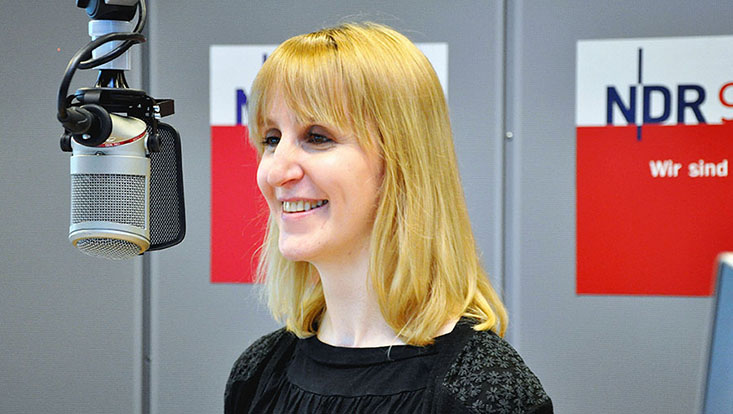 Mascha jacoby vor einem Mikrofon, im Hintergrund Studio des Radiosenders NDR 90,3