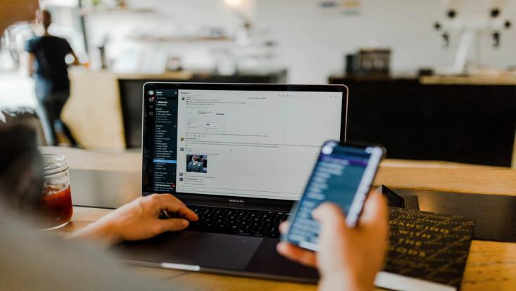 Mann nutzt Laptop und Computer gleichzeitig zur Kommunikation