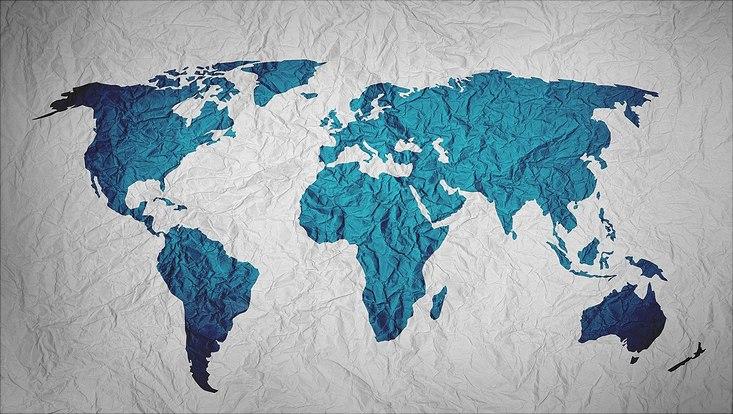 zerknittertes weißes Blatt Papier mit Umrissen der Welt in blau