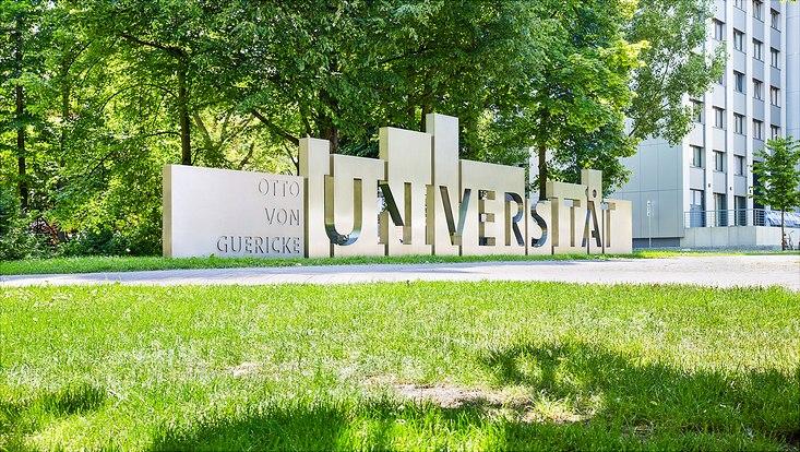 Schriftzug der Universität Magdeburg auf einer Wiese