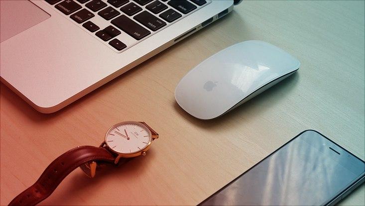 handy laptop und uhr liegen nebeneinander auf tisch