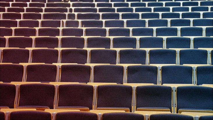 Das Bild zeigt leere Sitzreiehen in einem Vorlesungssaal.