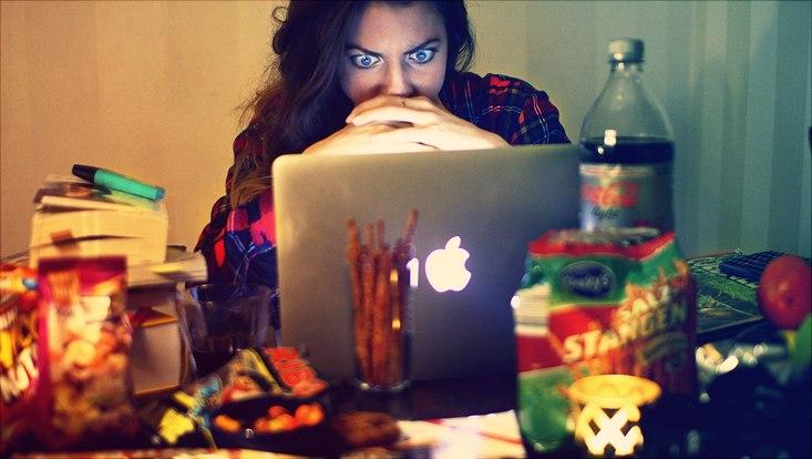 Das Bild zeigt eine Studentin vor ihrem Laptop umgeben von einem Berg von Süßigkeiten.