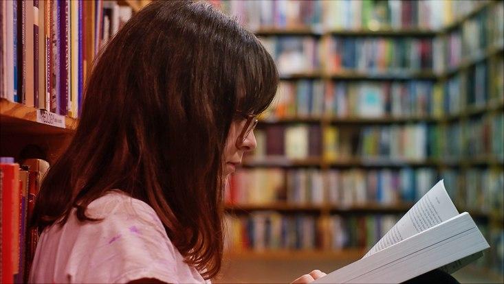Das Bild zeigt eine lesende Studentin zwischen Bücherregalen in der Bibliothek.