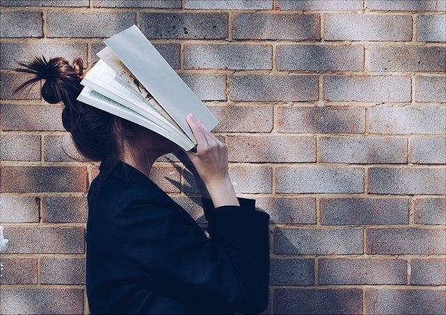 Frau mit Buch vor Gesicht