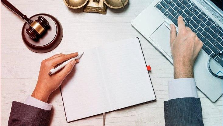 Das Bild zeigt Hände, einen Laptop sowie Symbolgegenstände der Rechtswissenschaft.