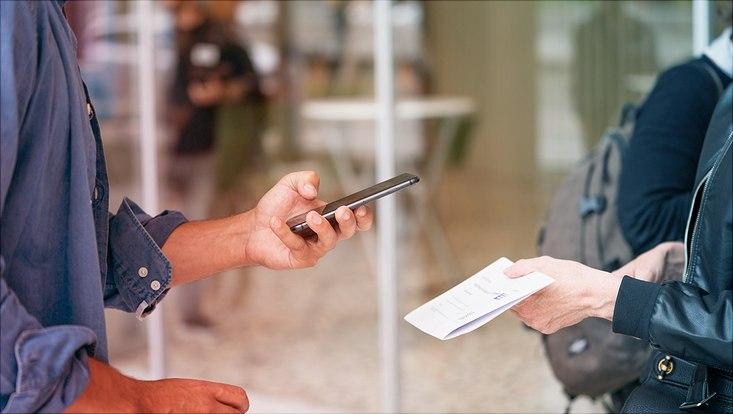 mann scannt mit seinem smartphone ein blatt papier