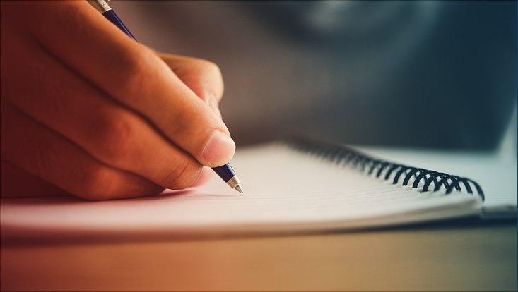 Das Bild zeigt eine Hand mit Stift beim Schreiben in ein Ringbuch.