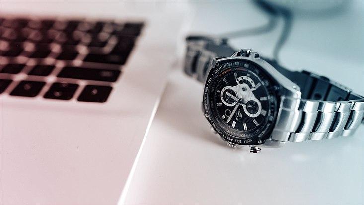 Das Bild zeigt einen aufgeklappten Laptop mit einer daneben liegenden Armbanduhr.