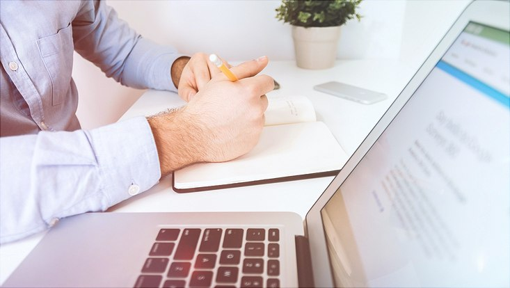 Hände eines Mannes mit Stift in der Hand vor Schreibblock und Laptop