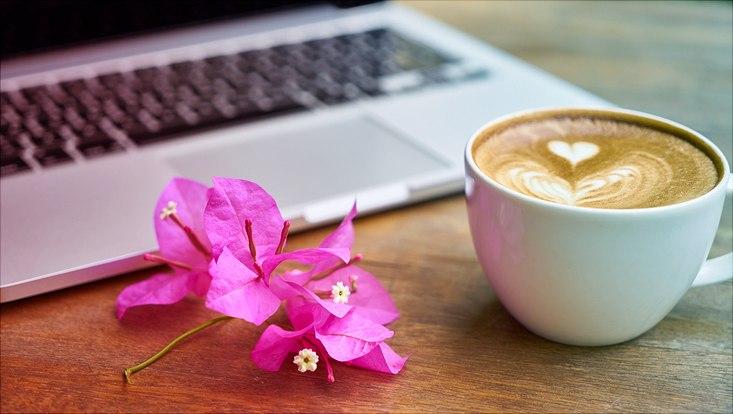 Das Bild zeigt einen aufgeklappten Laptop mit einem Cappuccino und einer Blüte davor.